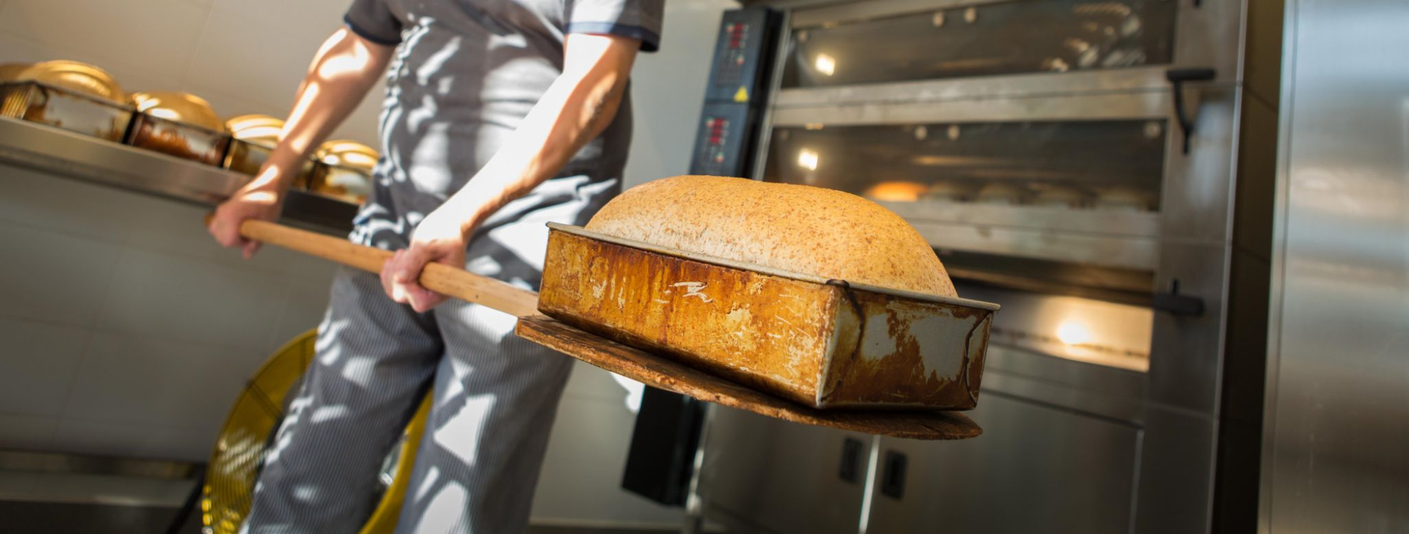 The freshly baked bread is removed from the oven.