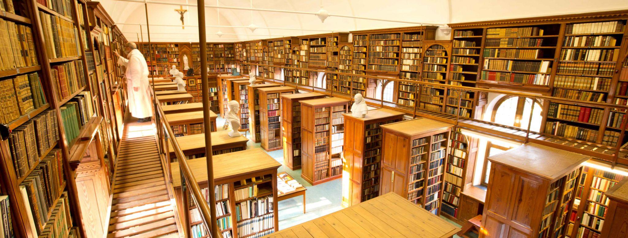 Un monaco sceglie un libro dalla biblioteca dell'abbazia di Westmalle