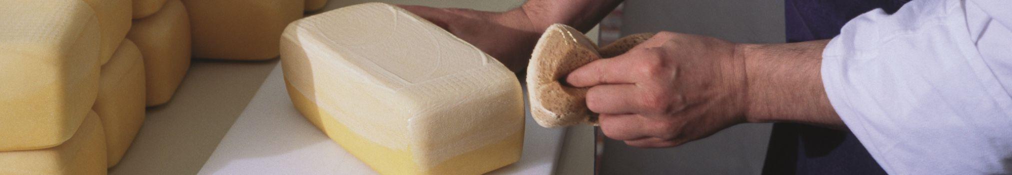 Dans la fromagerie, un frère met une couche de protection sur un fromage trappiste
