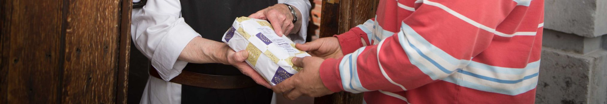 A brother sells a Trappist cheese at the abbey gate.
