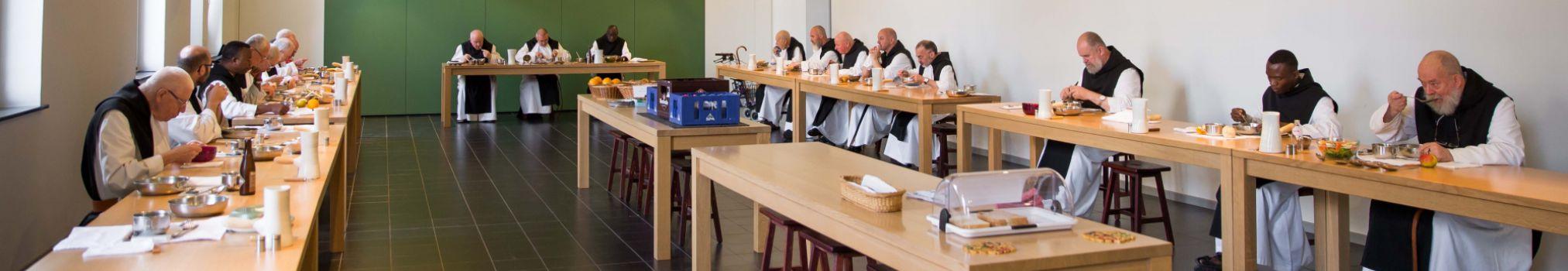 Monjes comen juntos tranquilos en el refectorio