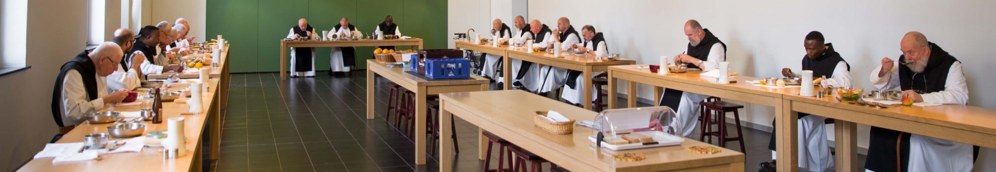 Monks share a meal in silence in the refectory.