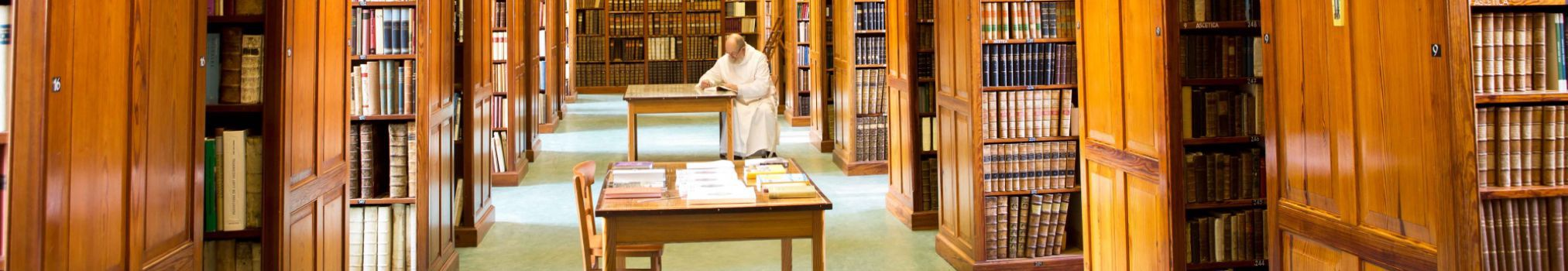 A monk studies and reads in the abbey library.