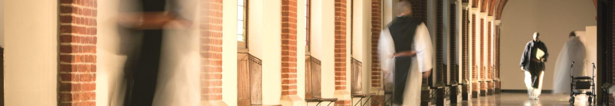 Moines se rendant à leurs tâches dans un couloir de l'abbaye