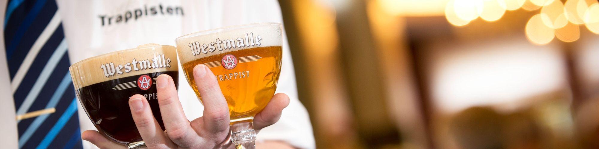 Camarero con un vaso de Westmalle Dubbel y Tripel.